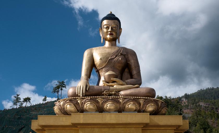 Seated Buddha sculpture in landscape.